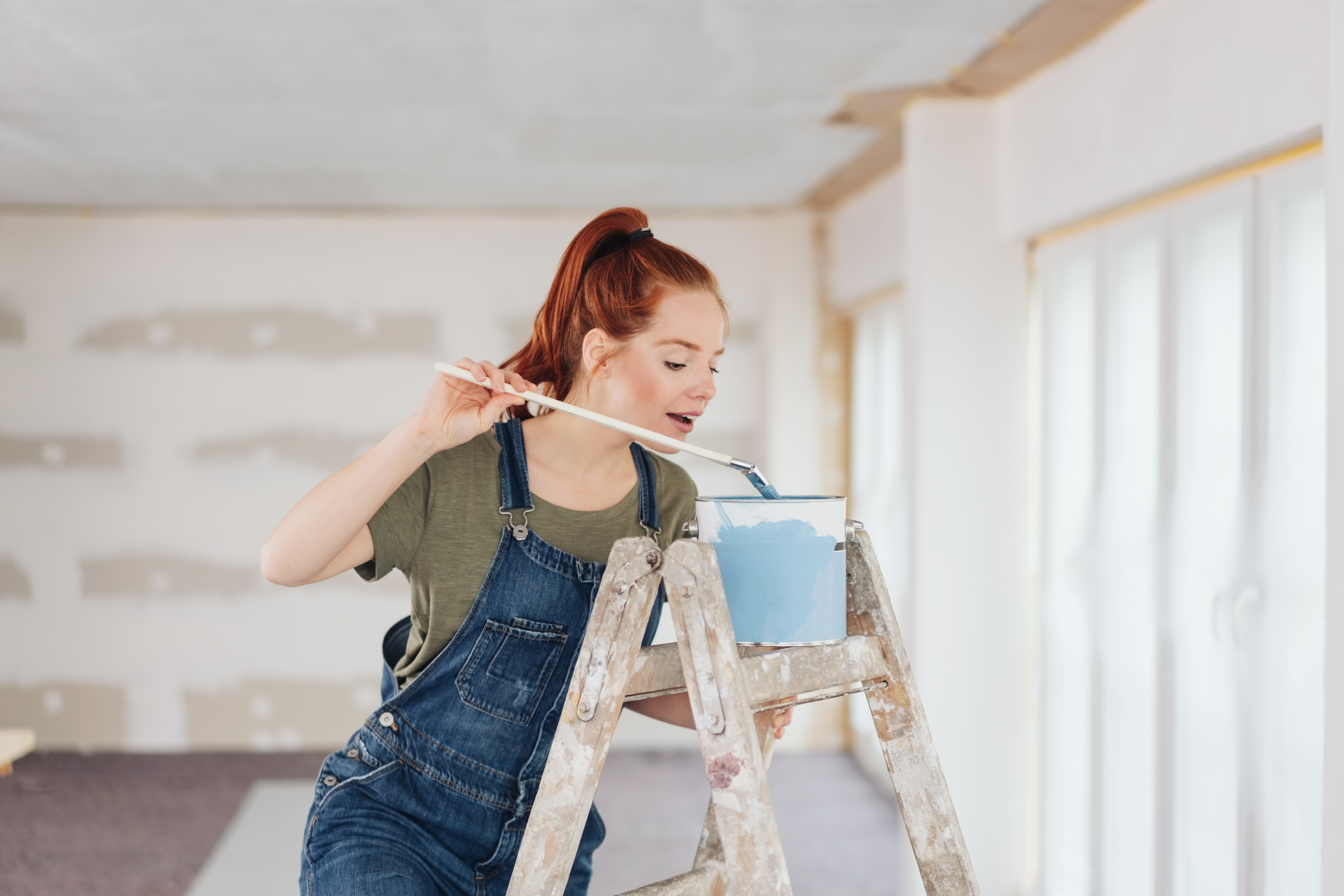Pretty young redhead woman doing DIY painting standing on a ladder peering into a tub of paint in an unfinished living room